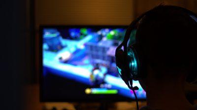 Mężczyzna gra na komputerze. Komputer jest z wynajmu komputerów gamingowych.